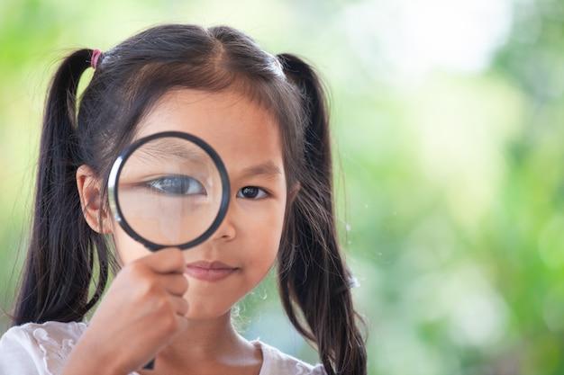 Close da menina asiática criança olhando através de uma lupa