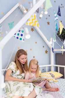 Close da menina bonita de 3 anos e sua jovem mãe lendo um livro na cama