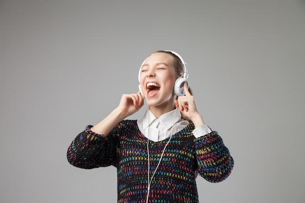 Close da menina com fones de ouvido cantando com a boca bem aberta em um fundo cinza