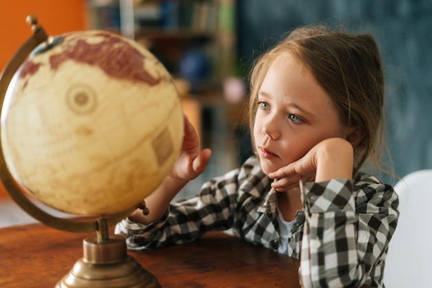 Close da menina criança curiosa girando um pequeno globo com interesse, olhando para os países do mundo