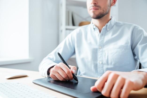 Close da mesa digitalizadora preta usada por um jovem designer sério no escritório