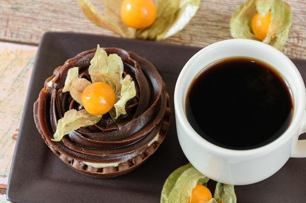 Close da minitorta com creme de mascarpone e ganache de chocolate, decorada com physalis, ao lado de uma xícara de café.