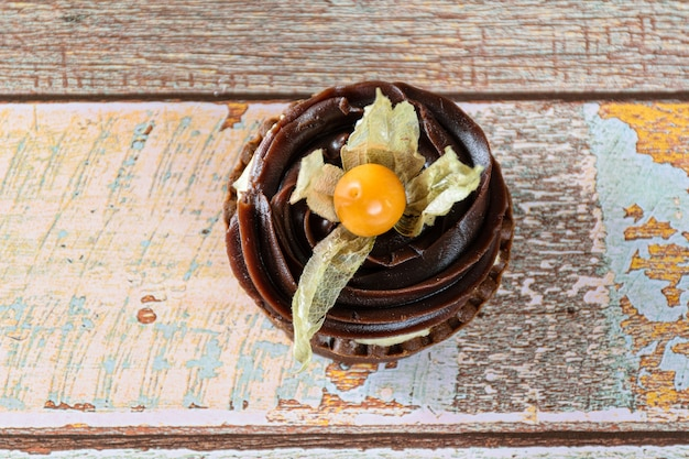 Close da minitorta com creme de mascarpone e ganache de chocolate, decorada com physalis (vista superior).