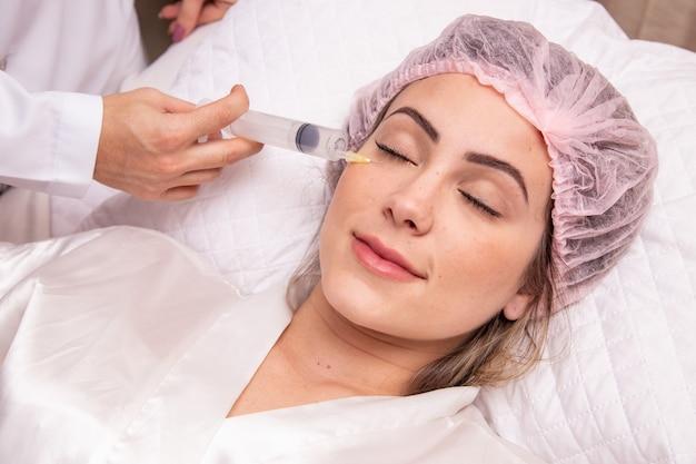 Close da mulher aplicando ozônio no rosto para tratamento cosmético.