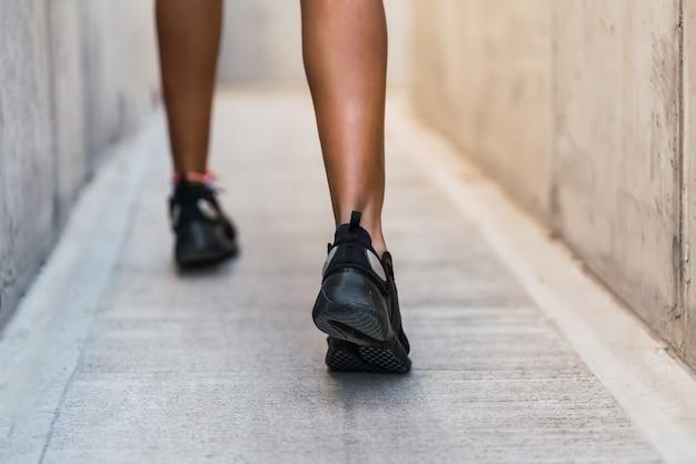 Close da mulher atleta correndo e fazendo exercícios ao ar livre