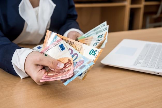 Close da mulher de negócios que deduz euros