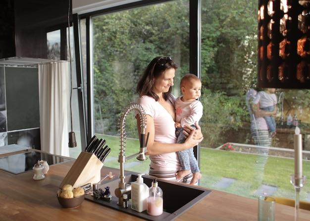 Close da mulher europen com seu bebê olhando pela janela