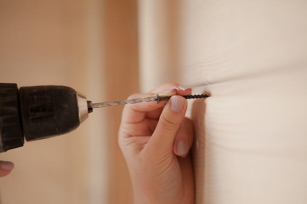 Close da mulher segurando o parafuso e a chave de fenda elétrica.
