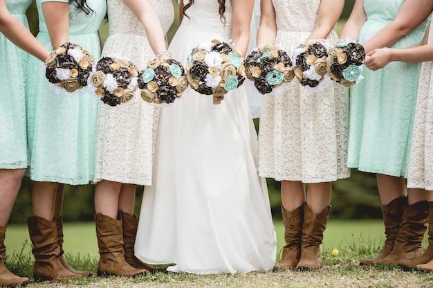 Close da noiva e das damas de honra segurando flores