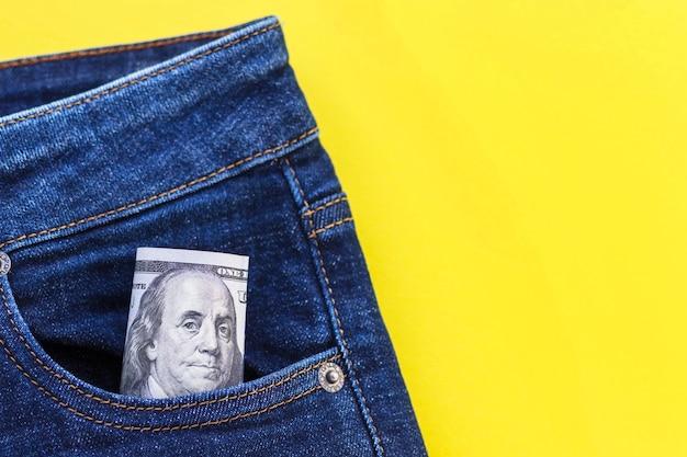 Close da nota de 100 dólares saindo do bolso da calça jeans.