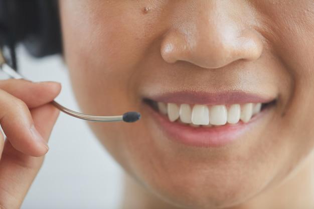 Close da operadora com fones de ouvido, sorrindo e falando ao telefone