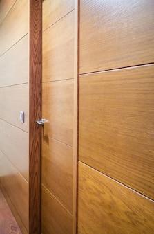 Close da parede de madeira com porta fechada e interruptor de luz