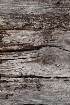 Close da parede de um celeiro de madeira com alguns defeitos