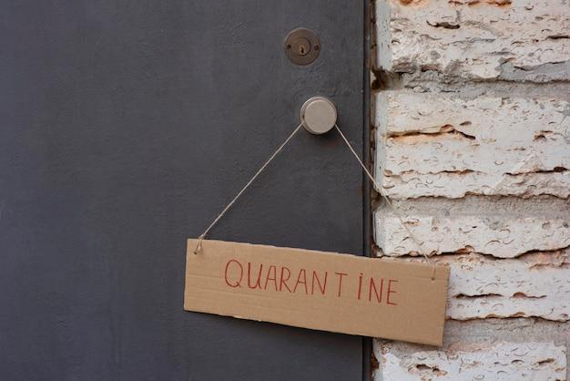 Close da placa de quarentena na porta da frente