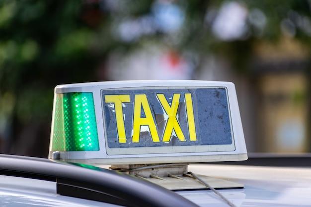 Close da placa do táxi quebrada presa ao teto de um carro