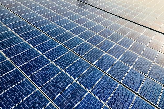 Close da superfície dos painéis solares fotovoltaicos azuis montados no telhado do prédio para a produção de eletricidade ecológica limpa. produção do conceito de energia renovável.