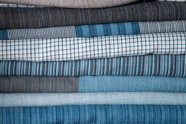 Close da textura de tecido de algodão com padrão branco e azul na prateleira de uma loja de tecidos naturais
