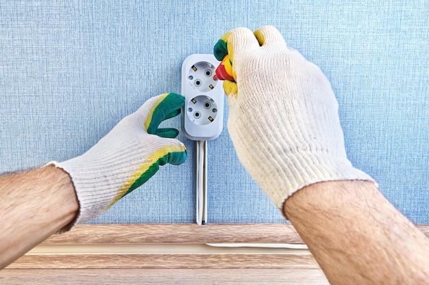 Close da troca da caixa do pattress da tomada de parede com a ajuda de uma chave de fenda pelo eletricista.