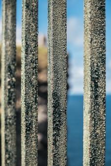 Close da velha cerca de metal enferrujado em um penhasco rochoso sobre o interminável mar azul em um dia ensolarado