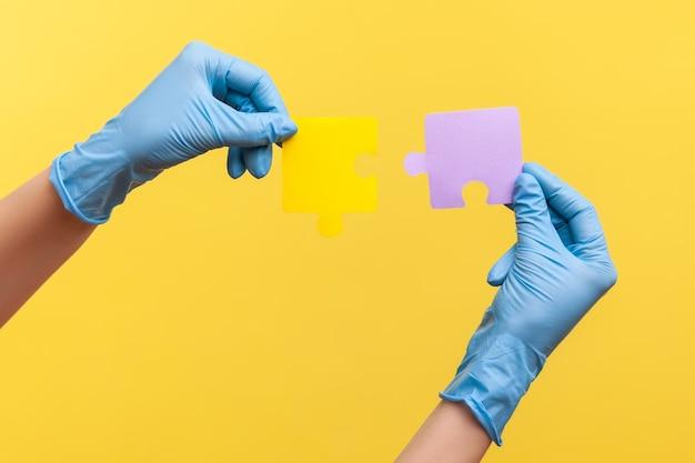 Close da vista lateral da mão humana em luvas cirúrgicas azuis segurando pieses de quebra-cabeça amarela e roxa.