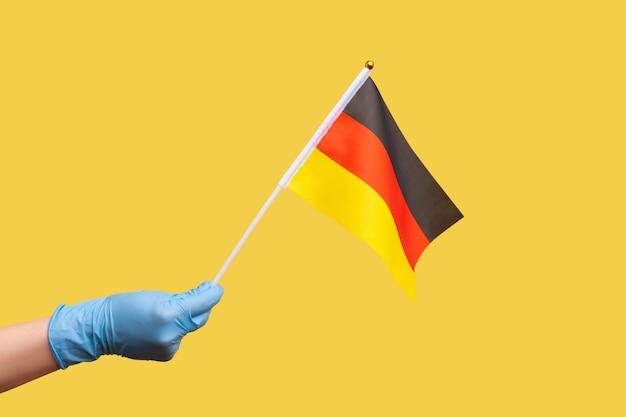Close da vista lateral do perfil de uma mão humana em luvas cirúrgicas azuis segurando a bandeira da alemanha