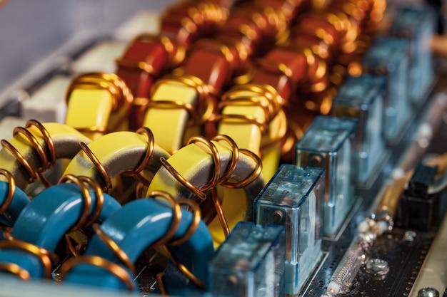 Close da vista superior de bobinas amarelas e vermelhas azuis enroladas em fio de cobre conectado a um microcircuito. conceito de fabricação de peças domésticas e produção de construção naval