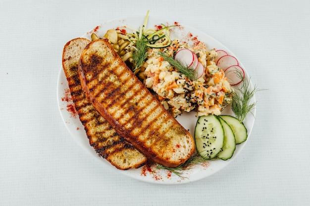 Close da vista superior de dois pedaços de pão torrado ao lado de uma salada com rabanete e pepino