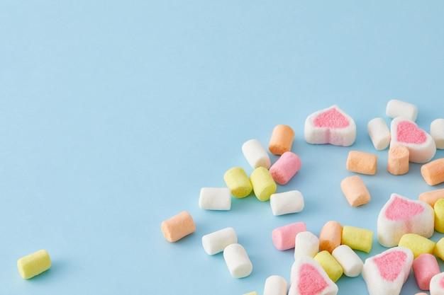 Close da vista superior de marshmallows coloridos isolados em um fundo azul