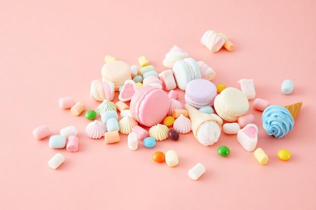 Close da vista superior de marshmallows coloridos, macaroons isolados em uma superfície rosa
