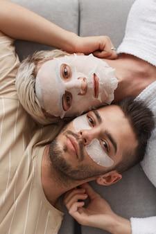 Close da vista superior de um jovem casal gay olhando para a câmera enquanto estão deitados no sofá juntos e usando máscaras faciais, conceito de beleza e cuidados com a pele