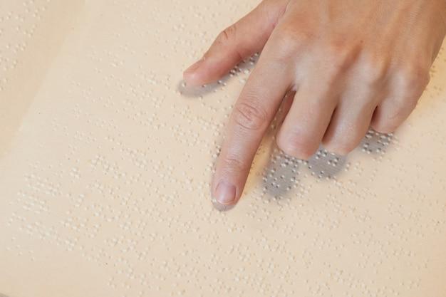 Close da vista superior de uma pessoa cega lendo um livro em braille