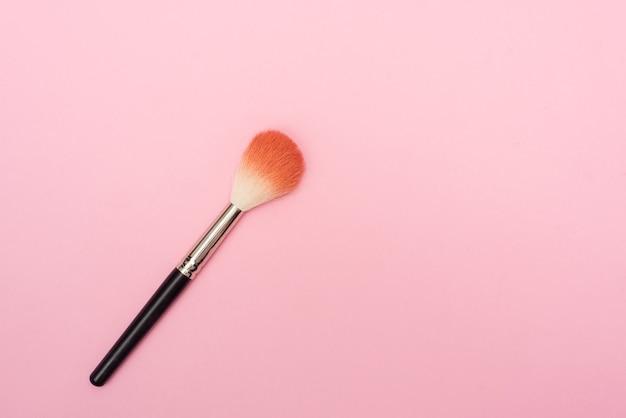 Close da vista superior do pincel de maquiagem em fundo de textura de plástico rosa pastel. conceito mínimo.