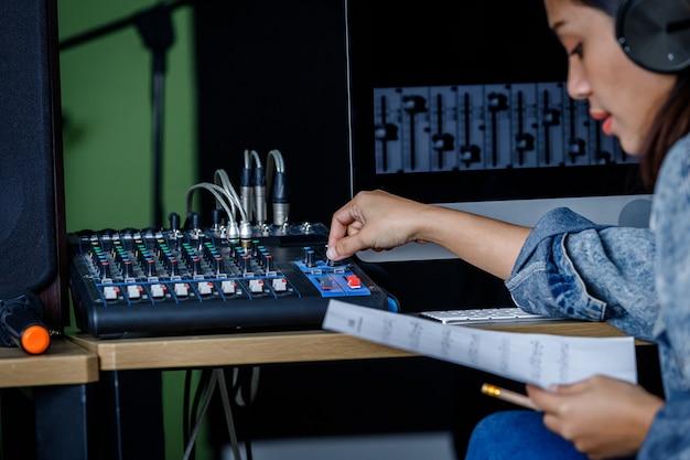Close da vocalista asiática usando fones de ouvido gravando uma música em frente ao equipamento da mesa de controle para gravação de som em um estúdio profissional