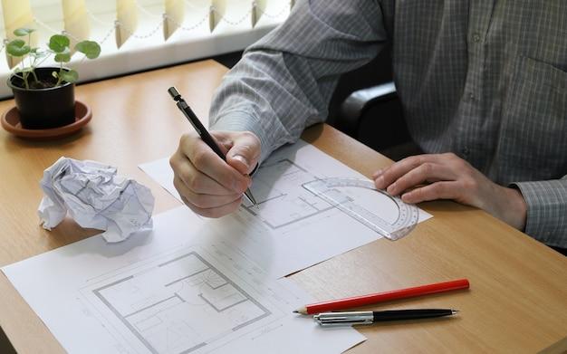 Close das mãos a pessoa faz anotações na planta arquitetônica