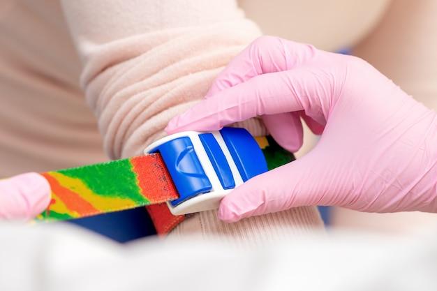Close das mãos da enfermeira apertando o arnês no braço no laboratório