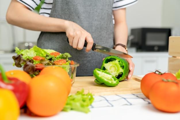 Close das mãos da mulher usando uma faca para cortar o pimentão e vários vegetais de folhas verdes