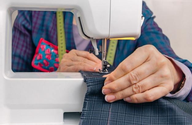 Close das mãos de costureira trabalhando com uma peça de roupa em uma máquina de costura
