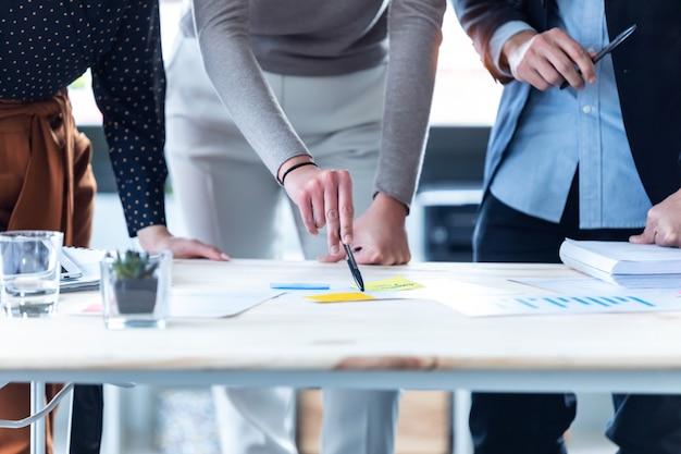 Close das mãos de empresários apontando para as estatísticas da empresa no escritório.