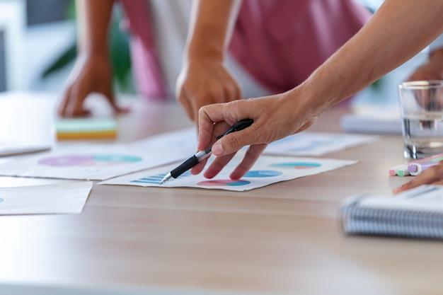 Close das mãos de empresários, apontando para as estatísticas da empresa no escritório.