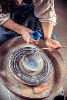 Close das mãos de oleiro com o produto em uma roda de oleiro