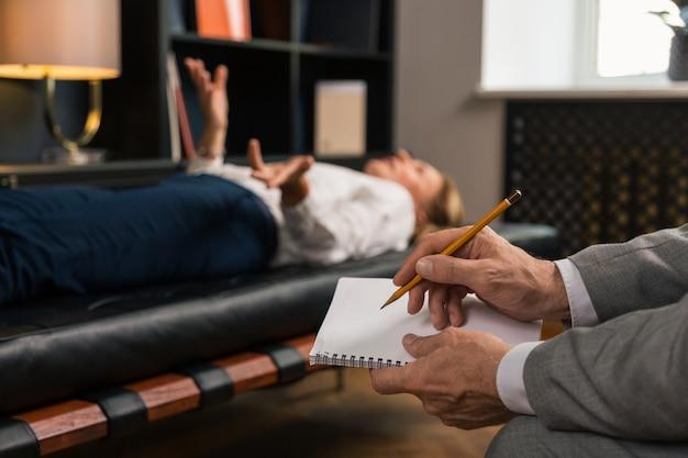 Close das mãos de psicoterapeutas masculinos fazendo anotações em seu bloco de notas enquanto está sentado ao lado de sua paciente deitada no sofá