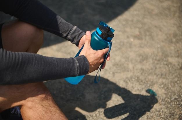 Close das mãos de um atleta masculino segurando uma garrafa azul cheia de água doce para se reidratar após um treino intenso de cardio e musculação