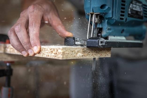 Close das mãos de um carpinteiro no processo de corte de madeira com um quebra-cabeças.