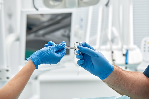 Close das mãos de um dentista e enfermeiro cirurgião sobre uma sala de cirurgia durante uma operação de implante dentário.
