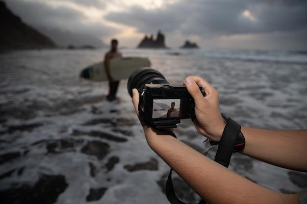 Close das mãos de um fotógrafo segurando sua câmera durante uma sessão de fotos com um surfista