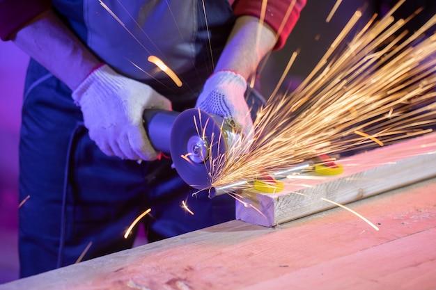 Close das mãos de um homem em luvas, moendo tubo metálico com faíscas em luz colorida