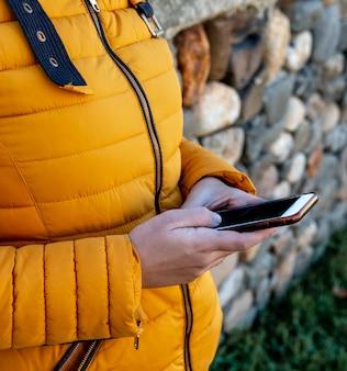 Close das mãos de uma jovem digitando em seu smartphone com grama e pedras