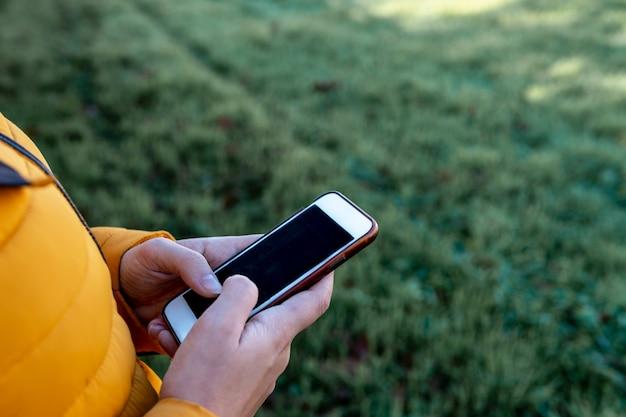 Close das mãos de uma jovem digitando em seu smartphone com grama na superfície