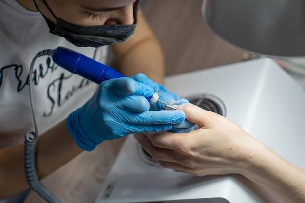 Close das mãos de uma manicure mestre em que uma ferramenta especial para remover verniz