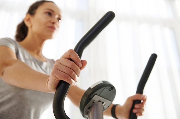 Close das mãos de uma mulher andando de bicicleta ergométrica durante um treino cardiovascular em casa